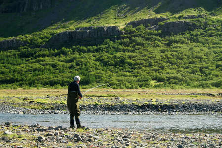 a man flyfishing in a great north atlantic salmon river just finished casting the line photo