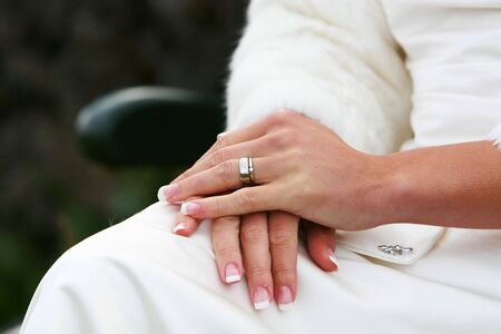 A wedding, bride sitting on a bench, with hands in lap, cropped shot of hands and wedding ring Stock Photo - 755357