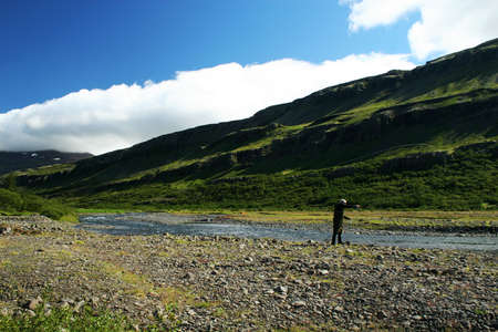 a man flyfishing in a great north atlantic salmon river , casting with the line in the air photo