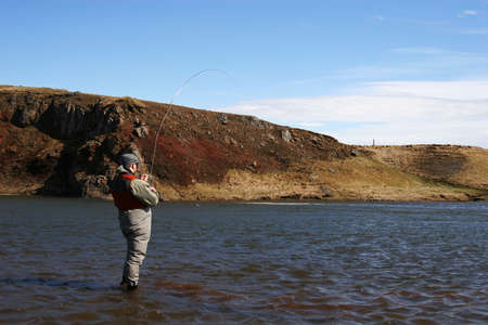 a man flyfishing in a great north atlantic salmon river figthing a big Salmon photo
