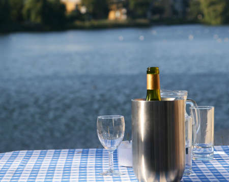 An open bottle of wine in a chilling bucket, glasses standing close by, set on a table with a lakescene in the background Stock Photo - 755352