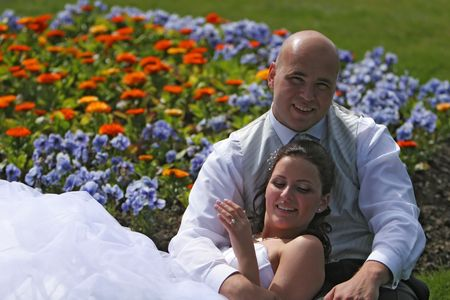 Newlywed couple, bride and groom sitting outside in sunshine, in the middle of a bed of colorful flowers Stock Photo - 3400168