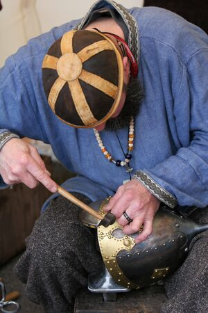 A craftsman chiseling inscription into a medieval soldiers helmet photo