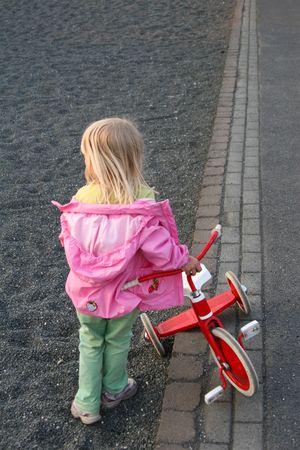 세 발 자전거 타기 후 백업 점점 작은 소녀 스톡 콘텐츠
