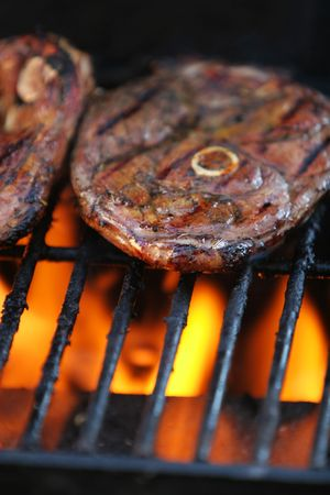 beneath: Lamb chops being barbecued on a gasgrill, flames visible beneath meat