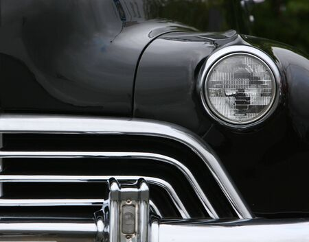 photograph of an old classic car in mint condition, frontal shot with one headlight and grill, black and chrome finish photo