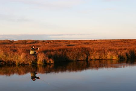 A man casting a fly in a calm river in autumn photo