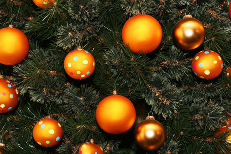 cropped shot of a christmas tree dotted with golden colored balls