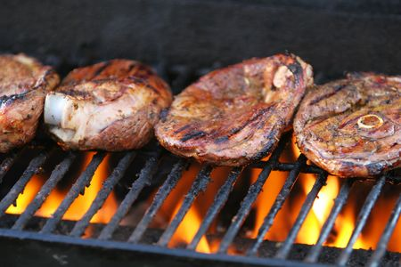 Lamb chops being barbecued on a gasgrill, flames visible beneath meat
