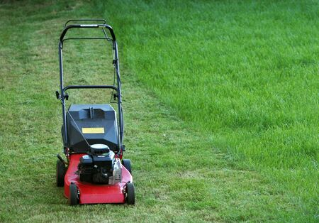 idle lawnmower standing on green grass, partly mowed but part still left to mow Stock Photo