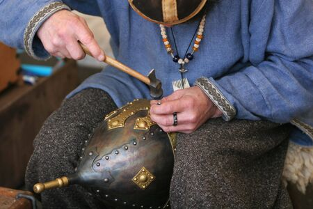 A craftsman making an armored medieval soldiers helmet photo