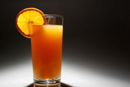 A Backlit glass of orange juice with a slice of orange Stock Photo