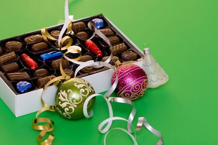 A box of fine chocolate on green background, christmas balls and decorations Stock Photo - 754771