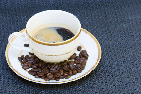 A cup of fine china porcelain , full of coffee, with coffee beans on the side Stock Photo - 754817