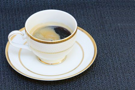 A fine china cup with high grade coffee in it, foam on top, the cup is standing alone on a plate on black bacground Stock Photo - 754813