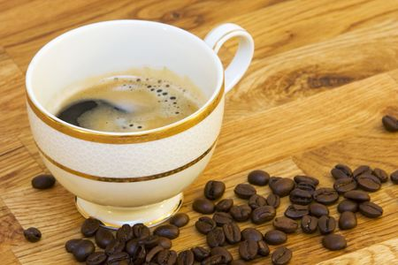 coffeebeans: coffee cup on natural wood,  foaming coffee in cup and coffeebeans lying around Stock Photo