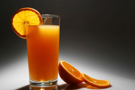 A glass of orange juice with a slice of orange lit from behind and above Stock Photo