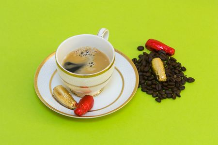 coffee cup on green background, chocolates and coffeebeans  photo