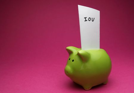 A green piggy bank on pink background, shot slightly from the side with an IOU note in it