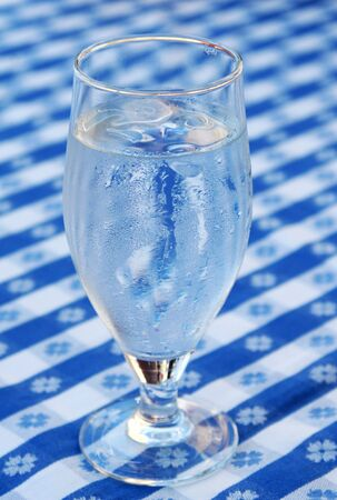 A glass of iced water, standing on a blue and white tablecloth, ice cubes in glass and condensed water on glass due to heat photo