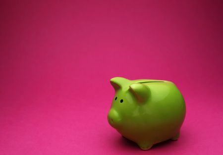 A green piggy bank on pink background, shot slightly from the side Standard-Bild