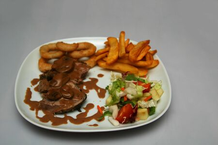 A dinner plate with a nice piece of meat with sauce on it, on the side Steakhouse fries, onion rings and salad Stock Photo - 1080450