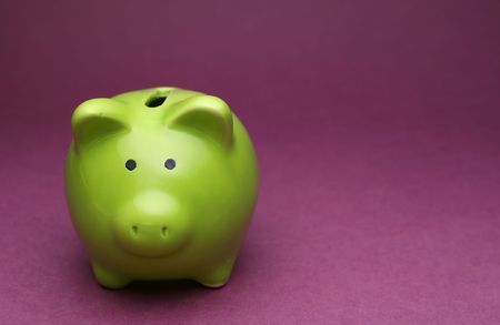A green piggy bank on purple background, shot from the front Stock Photo
