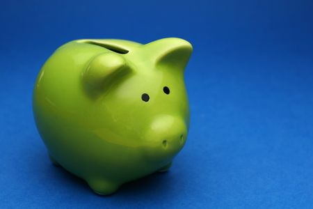 A green piggy bank on blue background, shot slightly from the side Standard-Bild