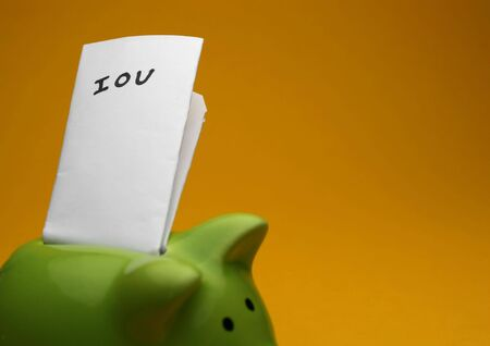 A green piggy bank on yellow background, shot slightly from the side note saying IOU