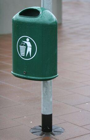 slob: A green trash bin in a city. The Bin is fastened to a lightpole.