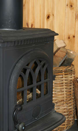 cast in place: a cropped shot of an old black cast iron fireplace with a basket full of firewood next to it Stock Photo