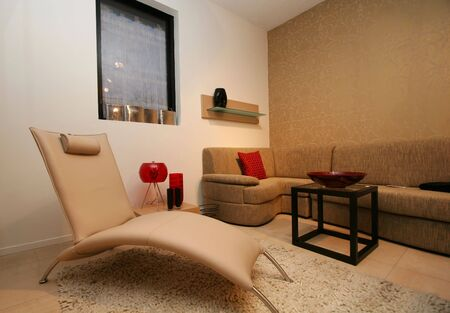uncluttered: living room, with clean uncluttered and modern design, white leather recliner and big sofa.