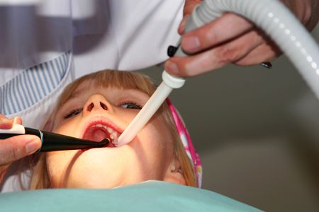 A young girl at the dentists, dentist taking a look into her mouth using various tools photo
