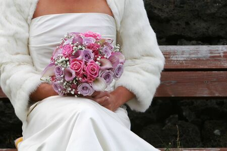 After the ceremony, bride sitting on bench with bridal bouqet in her hands, waiting for her husband to join her Stock Photo - 1080761