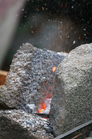 ancient blacksmith: A craftsmanblacksmith working metal the oldfashioned way, with hammer and anvil and open fire, sparks flying off fireplace Stock Photo