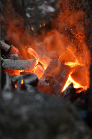 A craftsmanblacksmith working metal the oldfashioned way, open fire for heating metal to hammer it into shape
