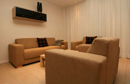 uncluttered: living room, with clean uncluttered and modern design, big sofa and chairs.