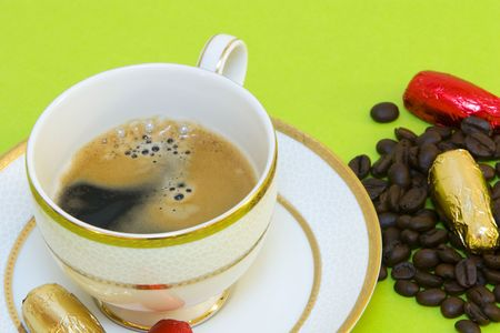 coffeebeans: coffee cup on green background, chocolates and coffeebeans