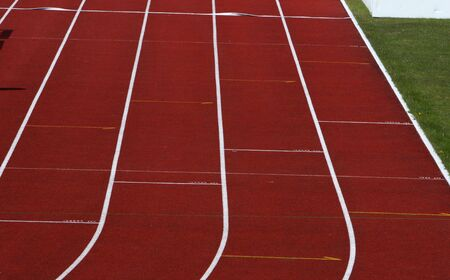 dividing lines: Straight red running track with white dividing lines part of grass visible Stock Photo