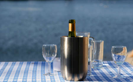 An open bottle of wine in a chilling bucket, glasses standing close by, set on a table with a lakescene in the background photo