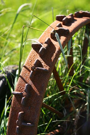 unused: Part of an old rusty iron wheel from discarded farm machinery, shallow focus, abstract  Stock Photo