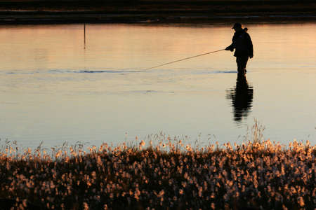 A man flyfishing in calm weather in twilight, sun lighting up the water and the near riverbank Stock Photo - 1090855