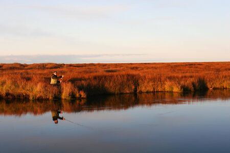A flyfisher casting his line in a calm river in autumn photo