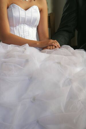 A wedding, bride and groom sitting holding hands after ring ceremony, cropped shot of hands Stock Photo - 1090877