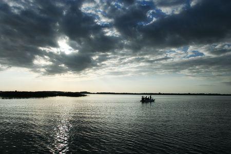 극적인 조명에 호수에 어부와 외로운 보트 스톡 콘텐츠