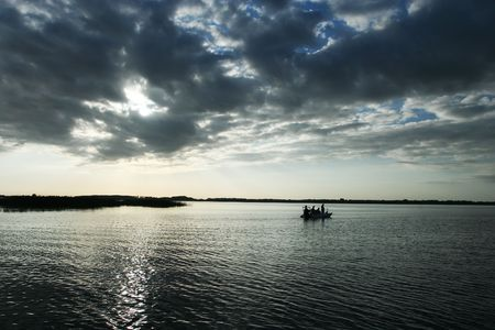 fishing scene: A lone boat with fishermen on a lake in dramatic lighting