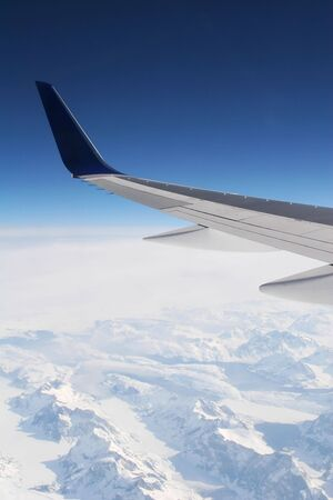 wing of a passenger jet at high altitude with snow covered mountain terrain in the mist below  photo