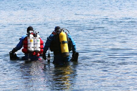 a pair of divers wading into water and preparing to scuba dive Stock Photo