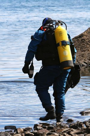 oxigen: a diver wading into water and preparing to scuba dive