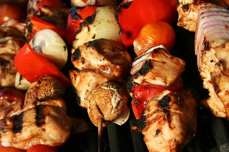 skewered meat and vegetables on a grilling pin ready to be grilled. Stock Photo